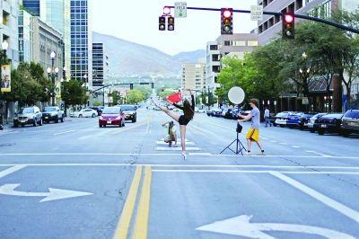 8月18日,一名芭蕾舞演员在美国盐湖城的马路上拍摄照片       新华社