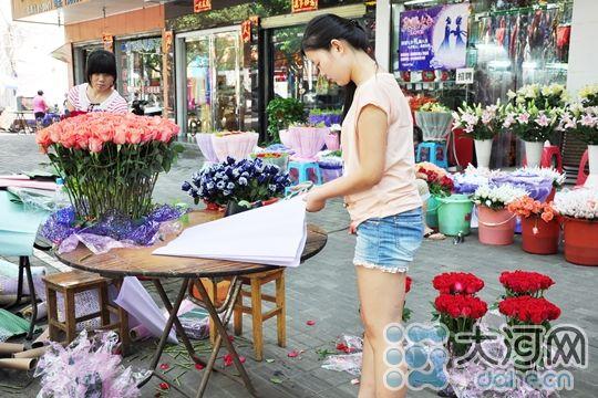 图为花店员工赶在七夕前包装更多花束