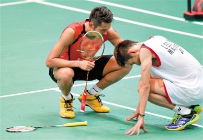 英雄气 决胜局中,李宗伟一度因伤蹲在地上,林丹见状穿过球场询问其伤情。 本版图片/Osports
