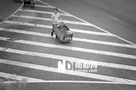 8月20日,广州火车站旁,一名熟食小贩看到城管慌忙离开,推着小车到环市西路上。南都记者 林宏贤 实习生 孙俊杰摄