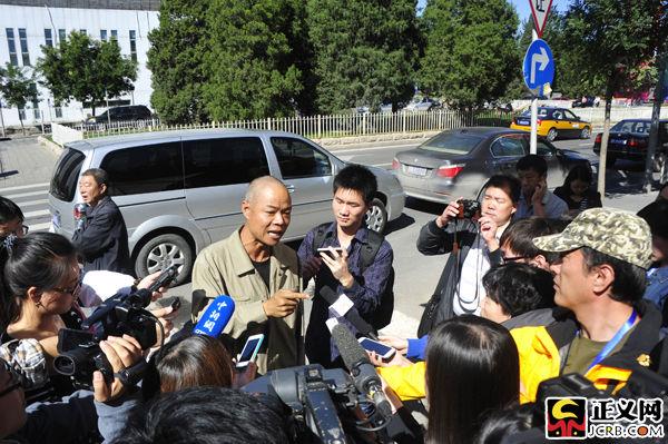 韩磊的朋友在法院门口接受媒体记者采访。闫昭摄