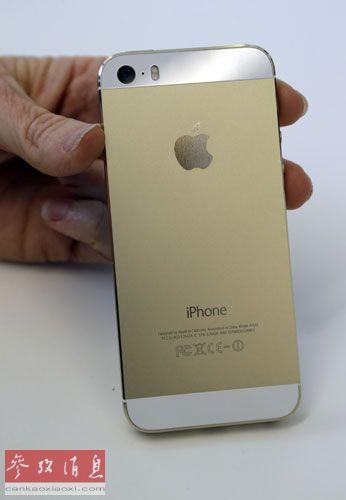 """资料图片:9月10日,在美国加利福尼亚州苹果公司总部举行的新品发布会上,一名苹果公司的代表展示iPhone 5S,这款颜色在中国也被称作""""土豪金""""。"""