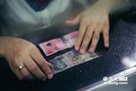 在清点过程中,会遇到许多破损钱币,王园园用人民币标准尺一张张进行测量,按照严格的标准和比例进行兑换。